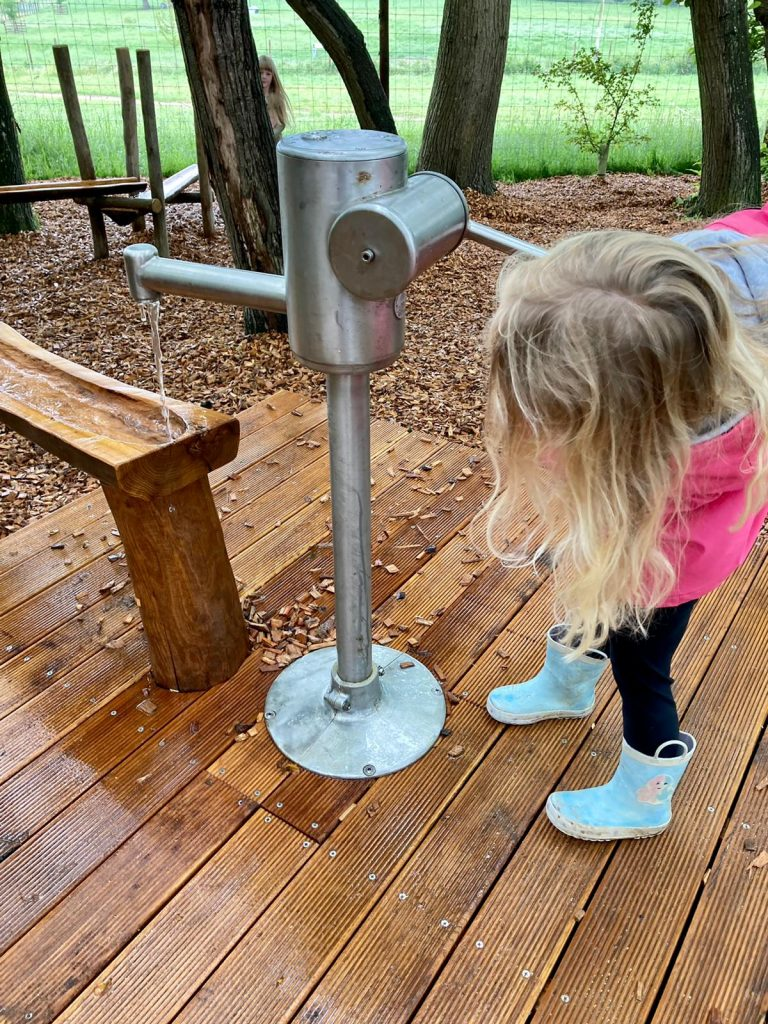 Girl at water pump in play ground